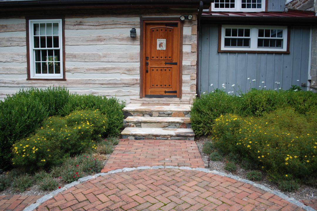 brick walkway stone steps between flower beds